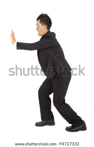 Businessman pushing away the wall