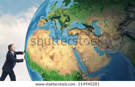 Businessman pushing big Earth planet. Elements of this image are furnished by NASA - stock photo