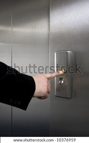 Businessman pushing elevator button - stock photo