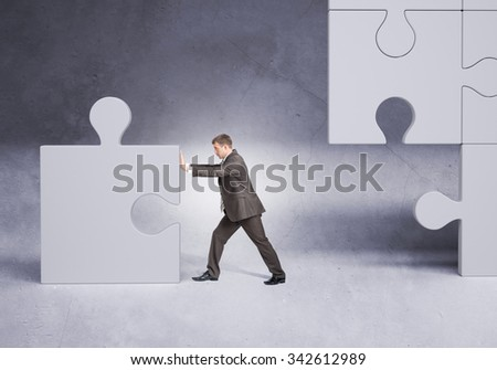 Businessman pushing puzzle piece on grey background