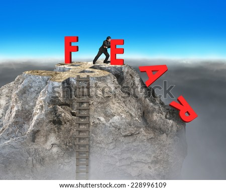 businessman pushing red fear word down with dollar sign and wooden ladder on top of rocky mountain, overcoming fear concept. - stock photo