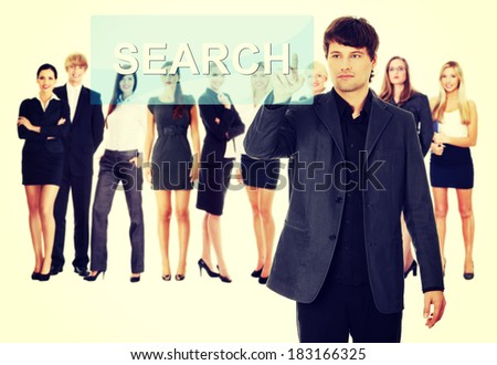 Businessman pushing SEARCH on a touch screen interface. Business team at background - stock photo