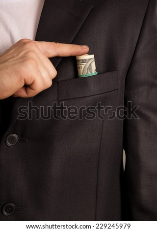 Businessman puts a bribe in his pocket, on a black background - stock photo