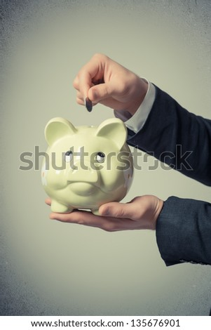 businessman putting a coin into a piggy bank on a gray background - stock photo