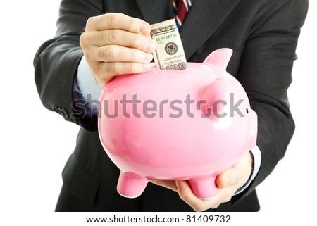 Businessman putting a hundred dollar bill in his piggy bank.  White background. - stock photo