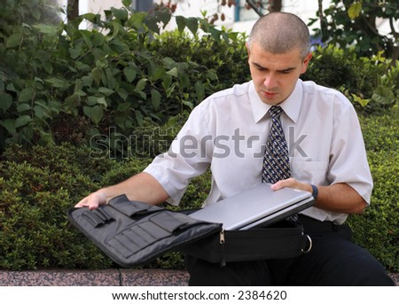 Businessman putting a latop in a bag after finishing some work in an urban park. - stock photo