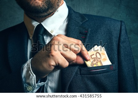 Businessman putting cash money in his pocket, elegant businessperson with euro banknotes - stock photo