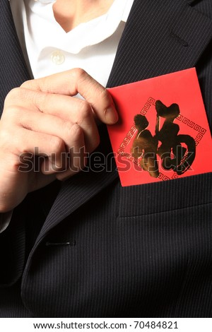 businessman putting chinese cash gift in his pocket - stock photo