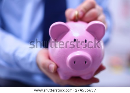Businessman putting coin into small piggy bank - stock photo