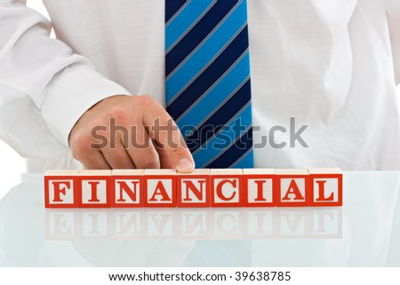 Businessman putting his finger on the word of FINANCIAL, made by blocks