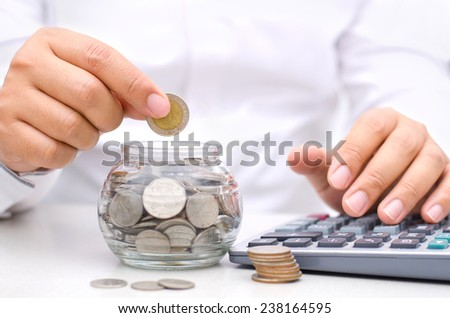 businessman putting money coins into glass jar bank for saving and insurance concept - stock photo