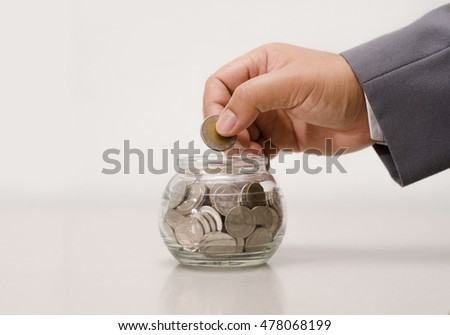businessman putting money coins into glass jar bank for saving concept