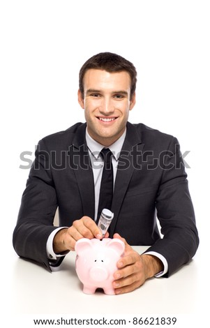 Businessman putting money in piggy bank - stock photo