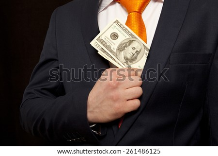 Businessman putting money in suit jacket pocket, concept for corruption, bribing - stock photo