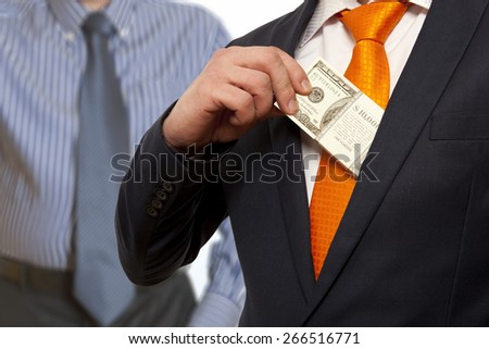 Businessman putting money in suit jacket pocket, concept for corruption, bribing - stock photo
