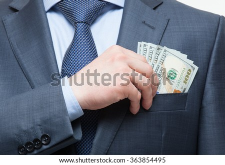 Businessman putting money in the breast pocket, closeup shot - stock photo