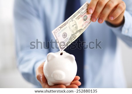 Businessman putting  money into a piggy bank isolated on white background - stock photo