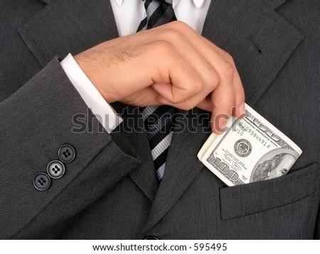 Businessman Putting Money Into Pocket - stock photo