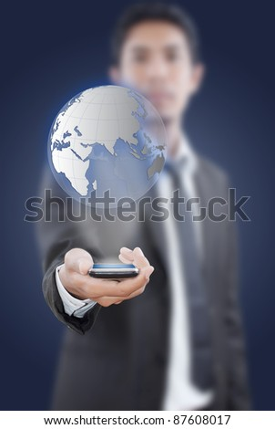 Businessman putting touch screen mobile phone with globe. - stock photo