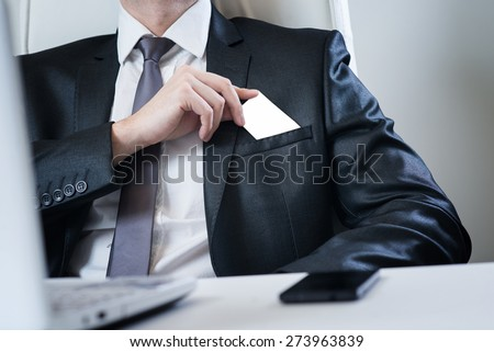 Businessman putting visit card in the pocket.  - stock photo