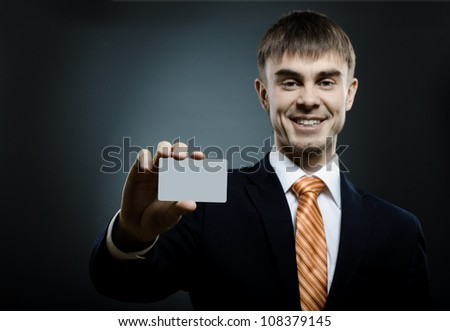 businessman  reach out on camera and show credit card or visiting card, smile - stock photo