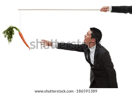 Businessman reaching for a carrot on the end of a stick with an exhausted look - stock photo