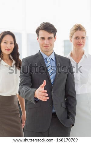 Businessman reaching hand out in front of his team in the office - stock photo