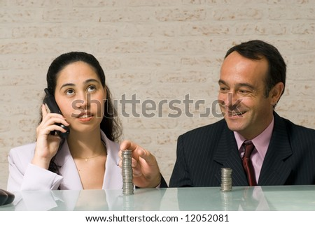Businessman reaching over and stealing money playfully from his female colleague while she talks on the phone - stock photo