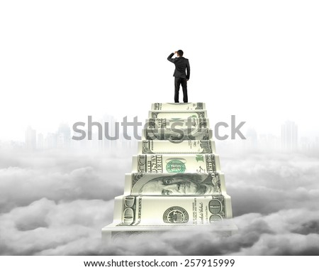 Businessman reaching the top of money stairs looking around gray cityscape with cloudscape background - stock photo