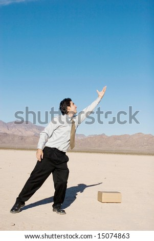Businessman reaching up with his hands - stock photo