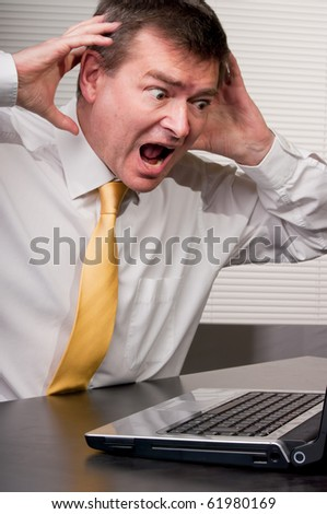 Businessman reacts in horror to laptop display or sudden revelation. Hands at head in gesture. Humor.