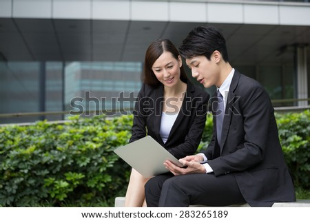 Businessman read on notebook computer with businesswoman