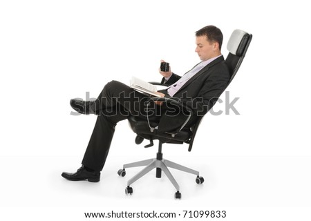 Businessman reading a book and drinking coffee sitting in a chair in a bright office. Isolated on white background