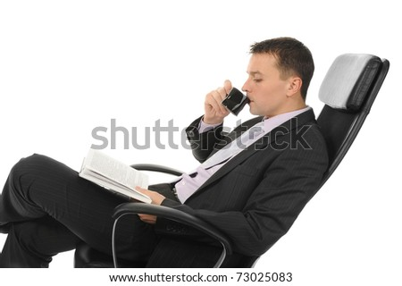 Businessman reading a book and drinking coffee sitting in a chair in a bright office. Isolated on white background - stock photo