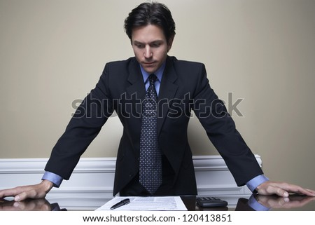 Businessman reading a document at office - stock photo
