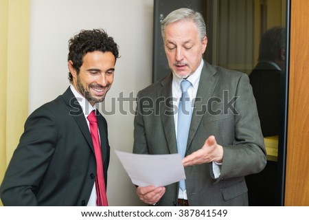 Businessman reading a document in their office - stock photo