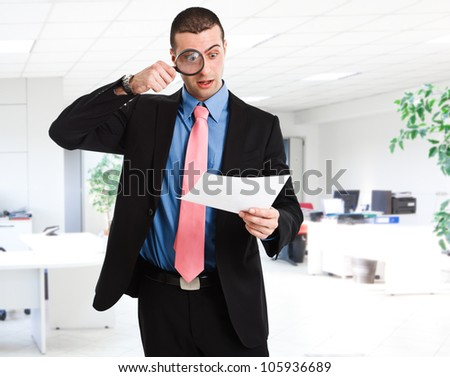 Businessman reading a document using a magnifying glass