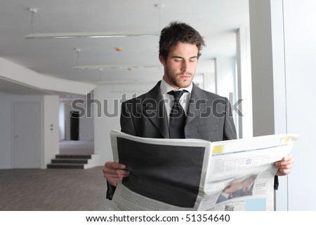 Businessman reading a newspaper - stock photo