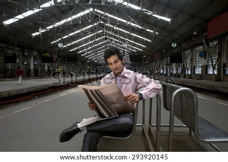 Businessman reading a newspaper at a train station - stock photo