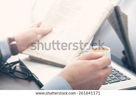 Businessman reading a newspaper at the office