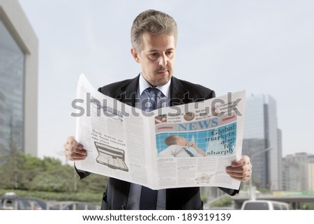 Businessman reading a newspaper, city backgrounds - stock photo