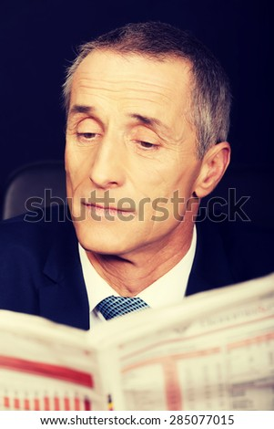 Businessman reading a newspaper in the office. - stock photo