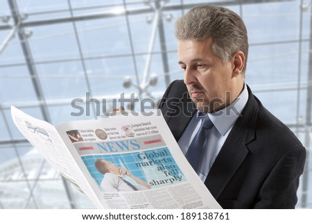 Businessman reading a newspaper, office backgrounds - stock photo