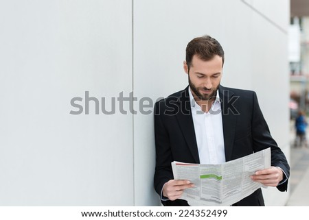 Businessman reading a newspaper on his lunch break as he leans against a white wall with copyspace - stock photo