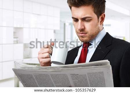 Businessman reading a newspaper while drinking coffee - stock photo