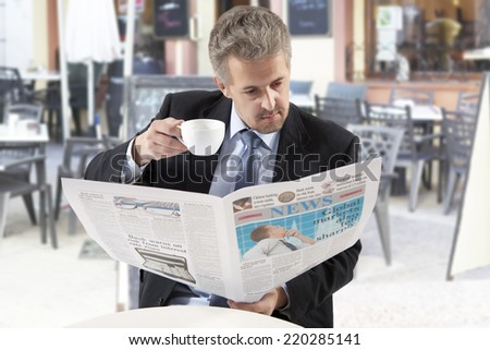 Businessman reading a newspaper while drinking coffee