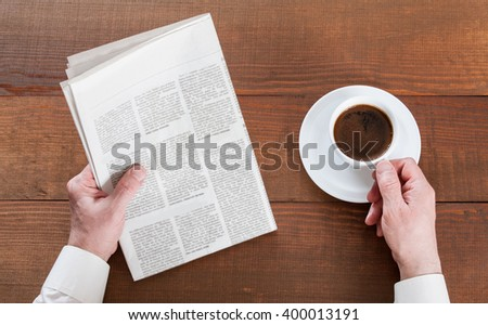 Businessman reading a newspaper with a cup of morning coffee, closeup shot