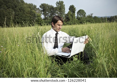 Businessman reading a paper on a large lawn - stock photo