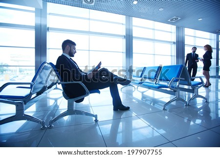 Businessman reading at the airport on background of colleagues talking by the window
