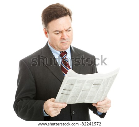 Businessman reading bad news in the newspaper.  Could be financial or political news.  Isolated on white. - stock photo